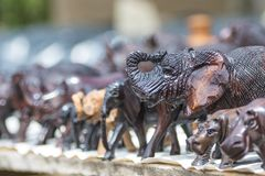 Close up of African Animals carved from wood in an open air market. Close up of African Animals hand carved from wood showing intricate detail with a blurred stock images