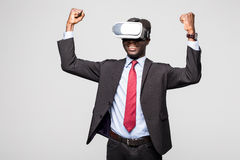 Close up of African employee wearing formal suit and goggles, experiencing virtual reality, stretching his arms up like win game. Royalty Free Stock Image