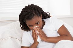 Girl Blowing Her Nose With Tissue. Close-up Of An African Girl Lying On Bed Blowing Her Nose With Tissue Stock Image