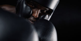 Close-up of african male boxer exercising. Close-up image of african male boxer wearing protective head guard and gloves against black background. Young man Stock Photos