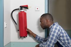 Male Professional Checking A Fire Extinguisher. Close-up Of African Male Professional Checking A Fire Extinguisher royalty free stock image