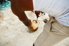 Close up african man peels coconut on the beach. African man peels coconut on the beach Royalty Free Stock Image