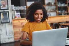 Young woman using laptop in cafe stock photography