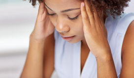 Close up of african young woman touching her head royalty free stock photography