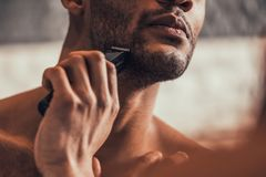 Close up. Afro-American Man Shaving in Bathroom. Close up. Afro American Man Shaving in Bathroom at Morning. Standing Man with Bare Torso in Bathroom. Personal Stock Photo