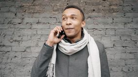 Close up afro-american man talking on phone. Handsome african-american guy in a coat and scarf speaking on mobile phone. Close up afro-american man talking on stock footage
