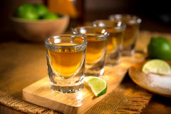 Close up of agave traditional Tequila shots flight with cut limes and salt. Golden Tequila shots with lime and salt served at mexican restaurant table to a party Stock Photo