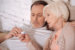 Close up of aged couple checking thermometer Royalty Free Stock Photography