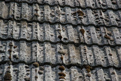Close up of aged roofing tiles on old house in village. A lot of moss on tiled roof of hovel. Countryside scene Stock Image
