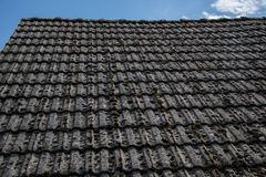 Close up of aged roofing tiles on old house in village. A lot of moss on tiled roof of hovel. Countryside scene Stock Photos