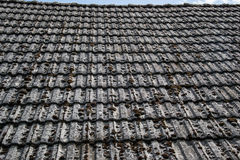 Close up of aged roofing tiles on old house in village. A lot of moss on tiled roof of hovel. Countryside scene Stock Images