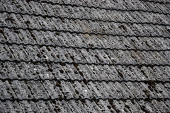 Close up of aged roofing tiles on old house in village. A lot of moss on tiled roof of hovel. Countryside scene Royalty Free Stock Images