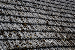 Close up of aged roofing tiles on old house in village. A lot of moss on tiled roof of hovel. Countryside scene Royalty Free Stock Photography