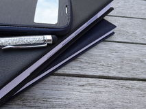 Close-up agendas, stylus pen and mobile phone on an old wooden table. Royalty Free Stock Images