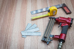 Close up air nail gun with measurement tools on wood. Background Stock Photography