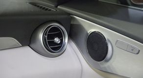 The close up of air vent and loudspeaker of luxurious car. The close up of air vent and loudspeaker of luxurious car, car interior stock images