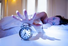Close up alarm clock with red haired woman turning it off Royalty Free Stock Images