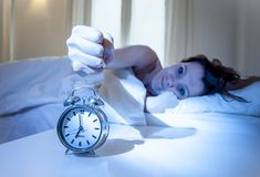Close up alarm clock with red haired woman turning it off Stock Image
