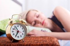 Close-up of alarm clock and sleeping young blonde woman in bright bedroom at home, morning stock photography