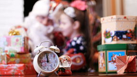Close-up of an alarm clock and a statuette of a snowman, in the background a cute pretty blonde girl with a pink bow in stock video