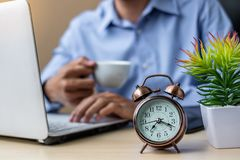 Close up alarm clock with young Businessman using laptop analysis marketing plan and drinking coffee in the morning. Business, stock photography