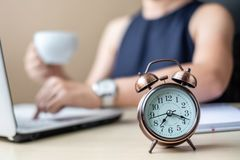 Close up alarm clock with young Businesswoman using laptop analysis marketing plan and drinking coffee in the morning. Business, royalty free stock photo