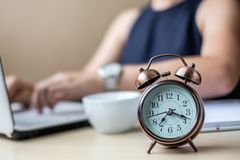 Close up alarm clock with young Businesswoman using laptop analysis marketing plan and drinking coffee in the morning. Business, royalty free stock image