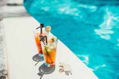Close-up of alcoholic drinks, ice and gin and tonic lemonade and mojito with lime served cold at pool bar Stock Images