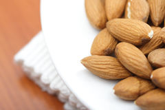 Close-up of almonds on white plate Stock Photo