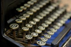 Close up of alphabet keys on a vintage manual typewriter. Close up of keys on a black vintage manual typewriter on a cobalt blue background. The `back space` stock images