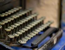 Close up of alphabet keys on a vintage manual typewriter. Close up of keys on a black vintage manual typewriter on a cobalt blue background royalty free stock photo