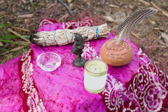 Shaman tools altar. Close up of altar with sage, water dish, candle, pottery rattle, feather and dancing Ganesha on the ground Stock Image