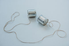 Close up of aluminium tin cans connected with rope on grey surface. Tin cans telephone Royalty Free Stock Photography