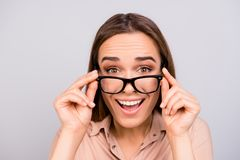 Close up of an amazed brunette young woman in beige formal shirt. And glasses, holding them, she is shocked, extremely happy, with wide open eyes, on pure light Stock Photography