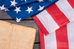c3a0a531bf08 Close up American flag and Bible. USA flag and vintage book on wooden table.