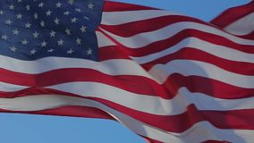 Close up of American flag waving. Close-up of an American flag flying in the wind against a background of clear sky. Waving United states of America famous flag stock footage