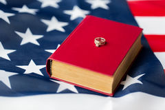 Close up of american flag, wedding rings and bible. Civil rights, family values and marriage concept - close up of american flag and wedding rings on book or Stock Photography