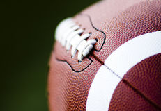 Close up of an american football. Against a black background Stock Images