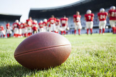 Close up of an american football. On the field, players in the background Royalty Free Stock Photos