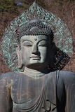 Close-up ancient metal carving of sitting peace buddha in front of tree mountain Stock Image