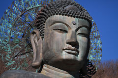 Close-up ancient metal carving of sitting peace buddha in front of tree mountain Stock Images