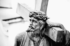Close Up Ancient Stone Statue Of Jesus Christ With Cross Isolated On White Background. Horizontal Image Royalty Free Stock Photography