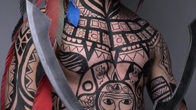 Close up of an ancient tribal warrior with two blades in his hands, war paint all over his body