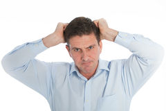 Close up Angry Businessman Pulling his Hair Out. Close up Angry Young Businessman in Light Blue Shirt Pulling his Hair Out While looking at the Camera. Isolated Royalty Free Stock Photo