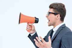 Close up. angry businessman shouting into megaphone. Isolated on white background stock images