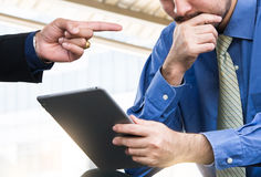 Close up, Angry businessman shouting to a colleague with tablet. Royalty Free Stock Photo