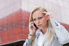 Close-up of angry businesswoman conversing on cell phone against office building Stock Images