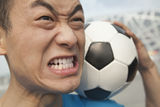 Close up of angry young man holding a soccer ball Royalty Free Stock Photo