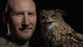 Close up of the animal trainer with an owl, black background. Big grey owl with grey feathers and orange eyes is sitting on its trainers hand stock video footage