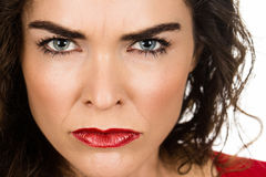 Close-up of annoyed angry woman. Close-up of a very annoyed and angry woman looking at camera royalty free stock images